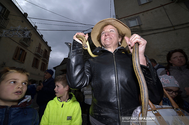 "People with snakes in hand before the procession.The feast of snakes. Process dedicated to the Saint Dominic, in the streets of Cocullo, in the Abruzzo region, Italy on May 1, 2019.<br /> <br /> <br /> <br /> The St. Domenico's procession in Cocullo, central Italy. Every year on the first  of May, snakes are placed onto the statue of St. Domenico and then the statue is carried in a procession through the town. St. Domenico is believed to be the patron saint for people who have been bitten by snakes:<br /> <br /> Italy, Cocullo, in the Province of L'A...quila, is at 870 meters a.s.l., along the railway line connecting Sulmona to Rome. The village rises alongside Mount Luparo (1327 meters) ""The valley opening in front of the village is surrounded by bare rocks, while on the other side, to the south, snow-capped mountain crests follow one after the other...""<br /> San Domenico Abate lived in the 10th and 11th centuries AD. Born in Foligno, in the Umbria region, he started his pilgrimages, preaching and ascetic practices in Central Italy, making miracles recorded by the word-of-mouth tradition. He died on 22 January 1031 and was buried in Sora.<br /> <br /> Cocullo snake charmers are over with their snake hunting. They proceeded through the During the procession on the first in May, before the snakes are placed all over the statue of St. Dominick, they will be fed with milk kept in containers with crusca. It is the snake that, most of all other elements, expresses an ancestral myth: the unknown aspect and unpredictability of the natural environment with man's innate need to achieve the dominance on his own habitat. <br /> <br /> Snakes and wolves were the emblems of Italic peoples like the Marsians and Irpinians. Some areas in Abruzzo, especially in the Sagittario valley, were under the menace of wolves and snakes, which for the local populations represented the uncertainty and anxiety of their existence that, together with the precariousness and hardships of life, were almost unbearable. Therefore the community adopted such magical-r"