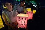 A young woman carries a floating candle lantern to the river on August 6, 2015, in Hiroshima, Japan. The lanterns, thousands of which were launched on the 70th anniversary of the atomic bombing of the city, carried handmade messages and drawings, conveying each person's prayers for peace and comfort for the victims of the violence.