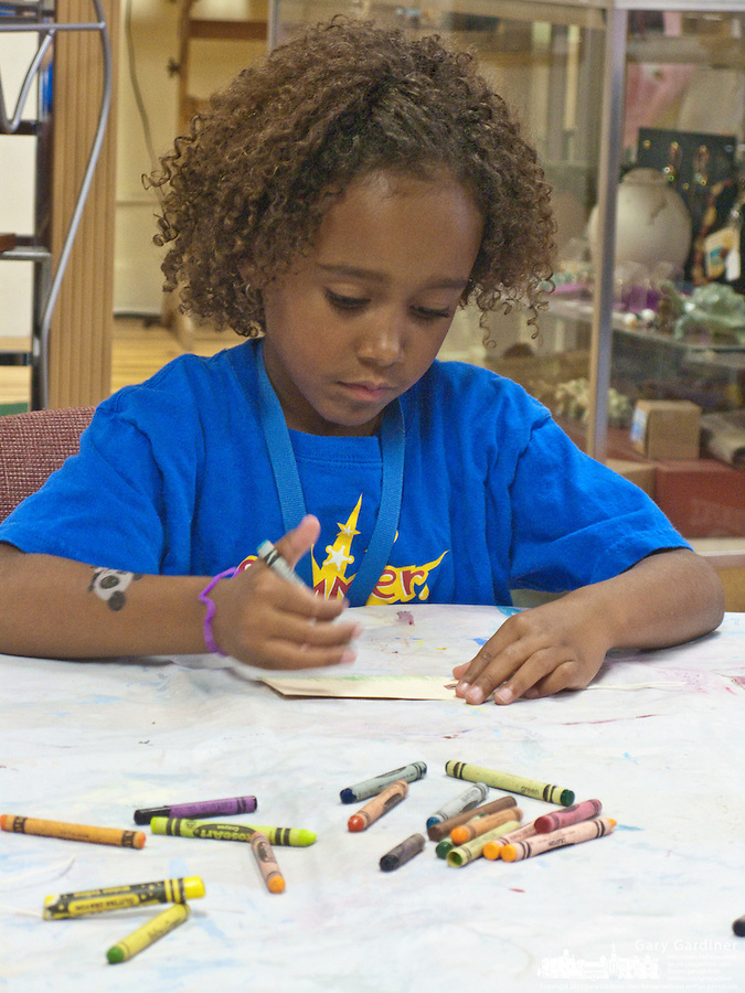 A young artists craws with crayons on her nametag that will be added to the wall of nametags created by all the artists attending yough classes at Gallery 202 in Uptown Westerville.