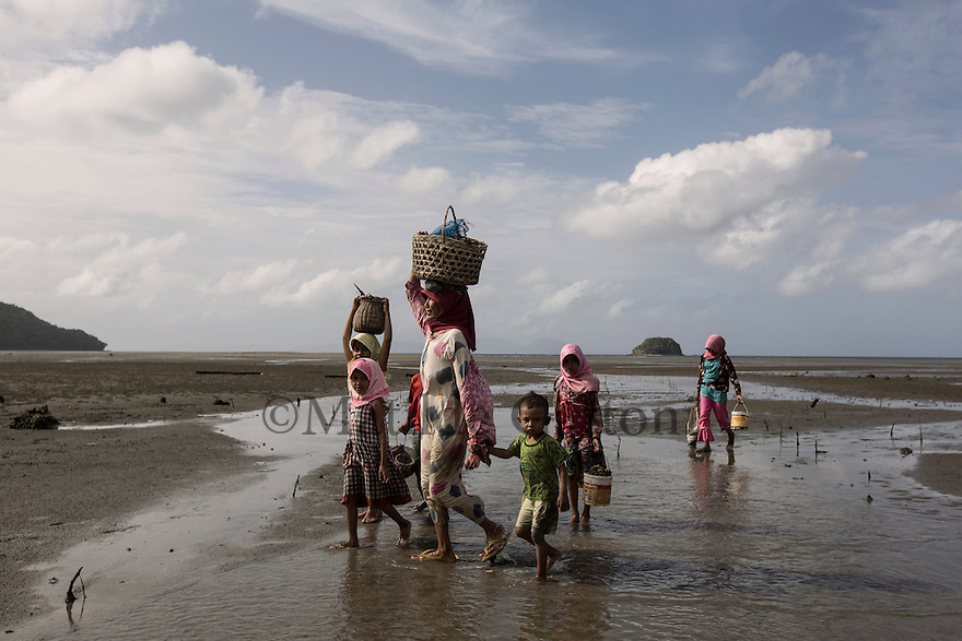 Indonesia - Sumatra - Aceh - Outskirts of Rigaih - A family walks back home after collecting mussels during low tide. Before the first wave arrived the water withdrew as far as the eye can see living km of land dry and covered with fish, thousands of people who were on the beach ran to gather the fish and were surprised and hit by the waters. The total number of victims was 184,000 confirmed, 230,000 estimated, 45,000 missing and 1,69 millions displacedIn Indonesia (almost entirely in Aceh): 130,000 confirmed, 167,000 estimated. 37,000 missing. More than 500,000 displaced, in Banda Aceh, 90,000 estimated dead.