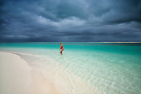 Woman walking in water. Turks and Caicos.
