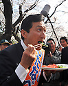 April 7, 2011, Tokyo, Japan - Miki Watanabe, a candidate running for governor of Tokyo, tastes a cucumber as he joins revelers in a toast under full-blown cherry blossoms at Tokyo's Ueno Park during his street campaign on Thursday, April 7, 2011. The cucumber is from Fukushima prefecture, from which shipment of leaf vegetables have been banned because of possible radioactive contamination from a nearby tsunami-damaged nuclear power plant.Watanabe, the founder of a chain of casual pubs, is running in the April 10 Tokyo gubernatorial election, attempting to make the big jump from business manager to big-time politician. (Photo by AFLO) [3609] -mis-.