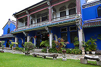 The mansion built by the merchant Cheong Fatt Tze at the end of 19th century has 38 rooms, 5 granite-paved courtyards, 7 staircases & 220 vernacular timber louvre windows.  Other features of the house include louvered windows, Chinese cut-and-paste porcelain work,  and Art Nouveau stained glass. The mansion was originally built with careful attention to the principles of Feng Shui: it faces the sea and has Penang Hill behind it;  it has water running through it.  The distinctive blue colour of the mansion is the result of mixing lime with natural blue dye made from the Indigo plant. The blue was very popular in the Colonial period and the dye was imported from India. The lime wash was very effective in a tropical weather as it absorbed moisture and cooled the house.