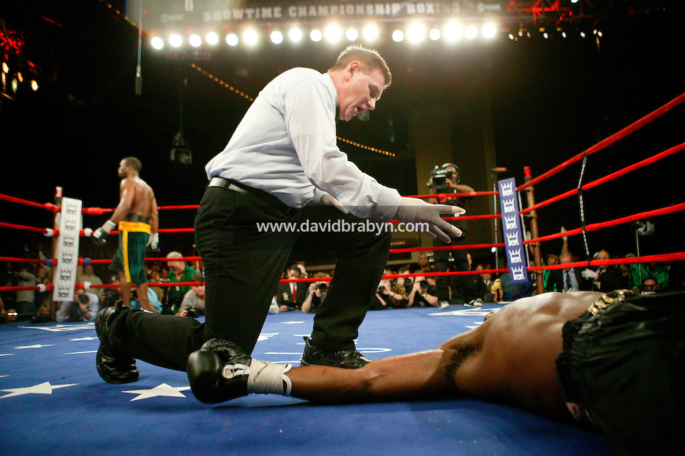 7 January 2006 - New York City, NY - The referee counts a knocked out Frenchman Jean-Marc Mormeck (R, foreground) as O'Neill Bell (green and yellow trunks) waits in the opposite corner during the World Cruiserweight Championship unification fight at Madison Square Garden in New York City, USA, 7 January 2006. O'Neil Bell won by KO in the 10th round.