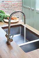 Detail of an unmounted Kubus sink by Franke has been matched with a Blanco tap and is ideally positioned opposite the hob in Kally Ellis's kitchen
