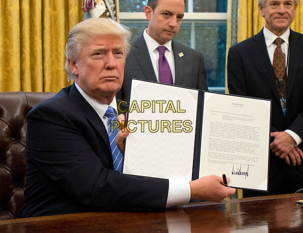 United States President Donald Trump shows the Executive Order withdrawing the US from the Trans-Pacific Partnership (TPP) after signing it in the Oval Office of the White House in Washington, DC on Monday, January 23, 2017.  The other two Executive Orders concerned a US Government hiring freeze for all departments but the military, and &quot;Mexico City&quot; which bans federal funding of abortions overseas.<br /> CAP/MPI/CNP/RS<br /> &copy;RS/CNP/MPI/Capital Pictures