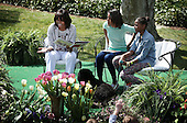 "First lady Michelle Obama (L) reads the story ""Cloudy with a Chance of Meatballs"" to children as daughters Sasha (R) and Malia (2nd L) look on during the annual White House Easter Egg Roll on the South Lawn of the White House April 1, 2013 in Washington, DC.  President Barack Obama and first lady Michelle Obama hosted thousands of people during the annual celebration of Easter. .Credit: Alex Wong / Pool via CNP"