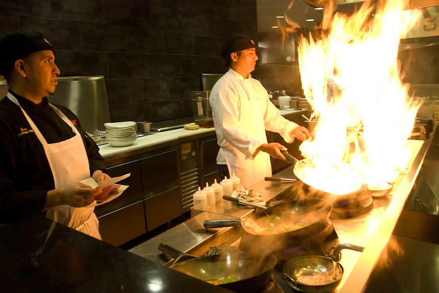 Chefs at the Stir Crazy restaurant in Brookfield, Wis. prepare their pans for cooking. The spectacle also entertains the customers. Ernie Mastroianni photo.