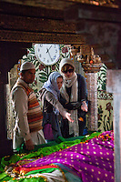 Fatehpur Sikri, Uttar Pradesh, India.  Inside the Mausoleum of Sheikh Salim Chishti.  Women Tossing Rose Patals on the Grave.