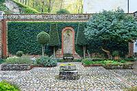 France, Sarthe (72),  Poncé-sur-le-Loir, jardin du château de Poncé en avril, patio, mur et lierre d'Irlande (Hedera helix, lauriers nobles taillés et laurier du Portugal à droite