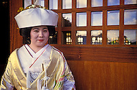 A young Japanese bride in traditional attire stands outside a temple in Honolulu.