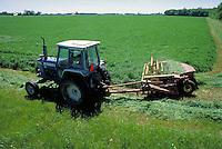overview of tractor pulling alfalfa harvester through field of green alfalfa. Michigan.