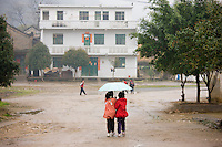 Young girls share an umbrella after leaving school in Fuli. China has a one child policy to limit population.