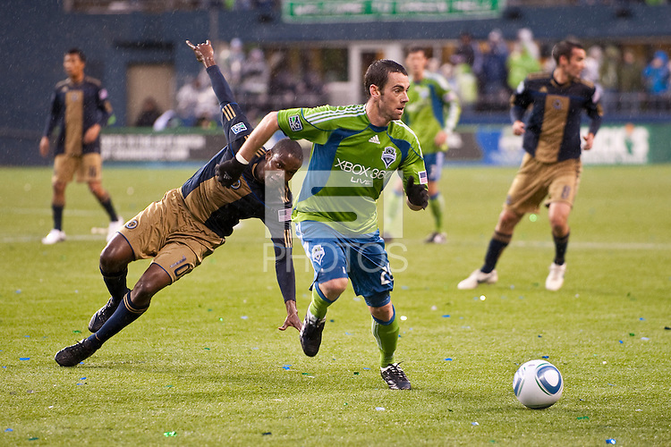Zach Scott (r) dodges a slipping Danny Mwanga (10) as the Seattle Sounders defeated the Philadelphia Union, 2-0, in an MLS match on Thursday, March 25, 2010 at Qwest Field in Seattle, WA. It was the Sounders home opener and the first regular season game for the expansion Philadelphia Union.