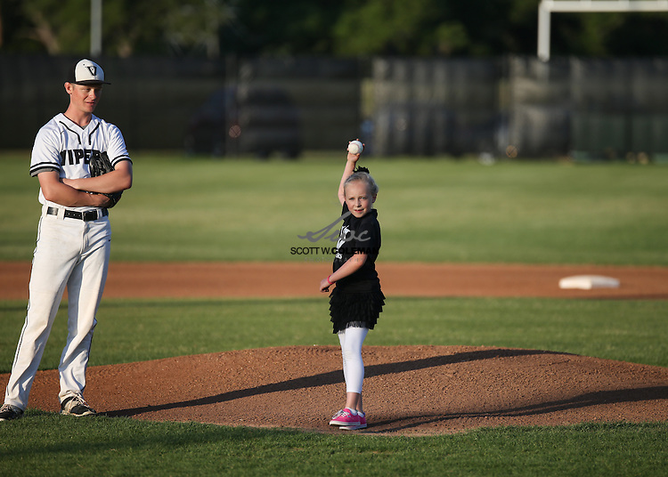 As senior pitcher Phillip Ahern (31)  watches, six-year-old Bayleigh McGee, daughter of Vandegrift baseball coach Allen McGee, throws out the first pitch before the high school baseball game between the Vandegrift Vipers and the Dripping Springs Tigers at Venom Field in Austin, Texas, on Friday, April 15, 2016.