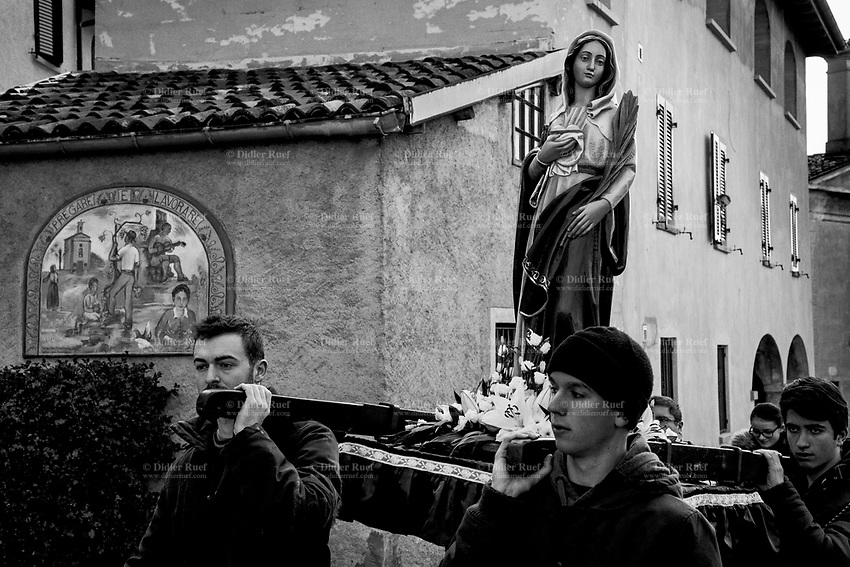 Switzerland. Canton Ticino. Cadro. Religious procession. Four young men carry a wooden sculpture of The Virgin Mary during the &quot;Festa patronale di Sant&rsquo;Agata&quot;. A mural painting on a private house&rsquo;s wall with the words Pray ( Pregare) and Work ( Lavorare), and various drawings with a church in the countryside, a musician and farmers at work in the fields. Mary was a 1st-century BC Galilean Jewish woman of Nazareth, and the mother of Jesus, according to the New Testament. Christians believe that she conceived her son while a virgin by the Holy Spirit. The Gospel of Luke begins its account of Mary's life with the Annunciation, when the angel Gabriel appeared to Mary and announced her divine selection to be the mother of Jesus. The Catholic Church holds distinctive Marian dogmas, namely her status as the Mother of God, her Immaculate Conception, her perpetual virginity, and her Assumption into heaven. Cadro is quarter of the city of Lugano and a former municipality in the district of Lugano. 4.02.2018 &copy; 2018 Didier Ruef<br /> <br /> .