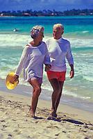 Senior couple walking down Kailua beach, Oahu