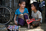 Two young girls sell bracelets and other crafts to tourists on the street in rural Laos, near Luang Prabang.