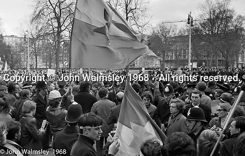 Protestors enter Grosvenor Square and scuffles with police begin, anti-Vietnam war demonstration march from Trafalgar Sq to Grosvenor Sq Sunday 17th March 1968. Two Vietcong flags are seen.  The Vietcong (National Liberation Army, NLF) was a political organisation and guerrilla army in South Vietnam which fought the Americans.