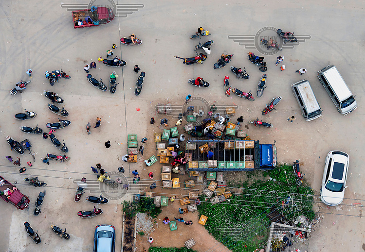 A poultry market in the city of Nanning. people park up their motorcycles =. /Felix Features