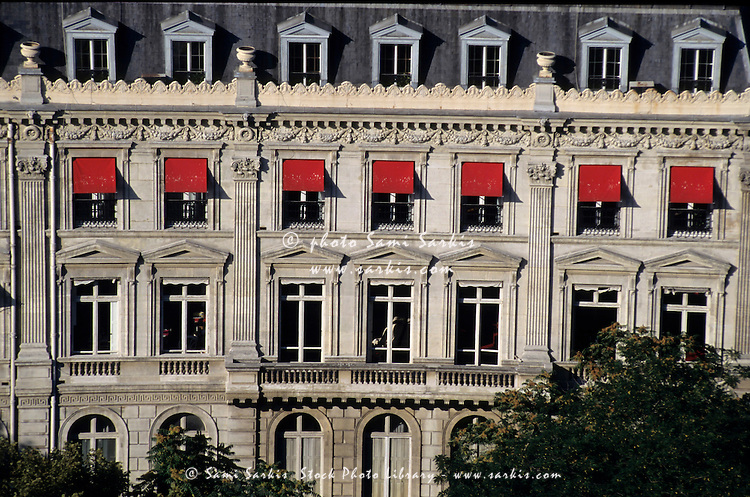 Exterior of a building with red awnings outside the windows, Paris, France.