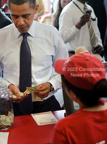 "Washington, DC - May 29, 2009 -- United States President Barack Obama pays for lunch at a ""Five Guys"" burgers and fries restaurant Friday, May 29, 2009 in Washington, DC.  President Obama traveled with his motorcade to the burger restaurant in Southeast Washington.  .Credit: Brendan Smialowski - Pool via CNP"
