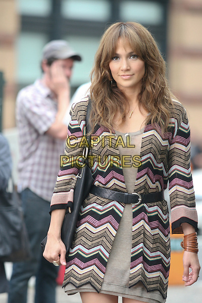 "JENNIFER LOPEZ.Filming on the set of ""The Back-Up Plan"" in Tribeca, Manhattan, New York, USA..July 16th, 2009.half length film set filmset on location black zig zag knit knitted patterned top cardigan waist belt pink grey gray dress suede purple beige .CAP/LNC/TOM.©TOM/LNC/Capital Pictures."