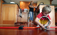 Ethan Jacobs, 5, builds a toy car track while his mother, Heather, makes dinner in the kitchen of their Polk City home.  Heather lost her husband, Eric, in a plane crash in 2006 when she was eight months pregnant with Ella and has since been raising her five young children on her own.