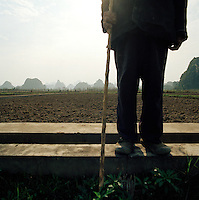 Farmer in front of karst limestone mountains, Guilin, Guangxi Province, China.