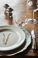 A place setting on the dining room table reveals a plate decorated with a pair of skis, a reminder of the snowy location of the chalet