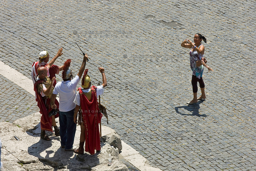 Rome continue to be one of the most visited city in the world..Roma continua ad essere una delle città più visitata al mondo.Tourist taking photos of gladiators in front of the Colosseum