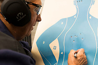 NWA Democrat-Gazette/CHARLIE KAIJO John Hundley of Garfield marks his shots, Friday, February 9, 2018 at Parker's Indoor Gun Range in Rogers. He circles his shots so he can distinguish where they landed at a certain practice distance.<br /><br />&quot;I just started here a couple weeks ago. Me and my grandson we target practice,&quot; Hundley said. &quot;I used to shoot in the military in 1970. Haven&Otilde;t done a whole lot since then.&quot;<br /><br />Hundley said he will be attending one of the concealed carry classes that Parker's Gun Range is hosting. A new enhanced carry law went into effect in January. He is part of a growing interest in concealed carry permits. <br /><br />The law allows concealed carry permit holders to carry their guns on to college campuses, bars and some public buildings. More than 70 concealed carry instructors received their certificates to teach the new 8-hour class in Arkansas. <br /><br />Parker's Gun Range hosts more than a dozen instructors who hold all or part of their concealed carry class including the shooting test at their range. The concealed carry class is a prerequisite for the enhanced class. Parker's will hold their first enhanced concealed carry class this Saturday. <br /><br />&quot;There's been a lot of phone calls, a lot of interest,&quot; Chuck Tripp, range safety office, said of the concealed carry classes. &quot;It&Otilde;s just been a steady growth. Classes are always full.&quot;<br /><br />All of the instructors who use Parker's range are either NRA certified instructors or NRA Range Safety officers Tripp said.