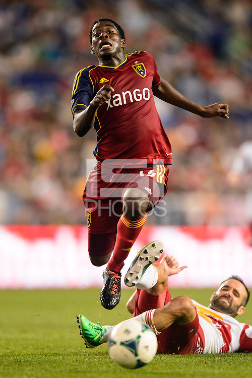 Olmes Garcia (13) of Real Salt Lake jumps over a tackle by Brandon Barklage (25) of the New York Red Bulls. The New York Red Bulls defeated Real Salt Lake 4-3 during a Major League Soccer (MLS) match at Red Bull Arena in Harrison, NJ, on July 27, 2013.