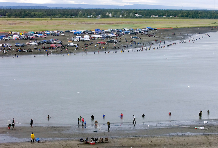 Dipnet fishermen line both banks of the Kenai River where it drains into Cook Inlet in downtown Kenai, Alaska. For several weeks each summer, the river's mouth takes on a carnival atmosphere as Alaskan residents come to the area from across the state to catch sockeye salmon.
