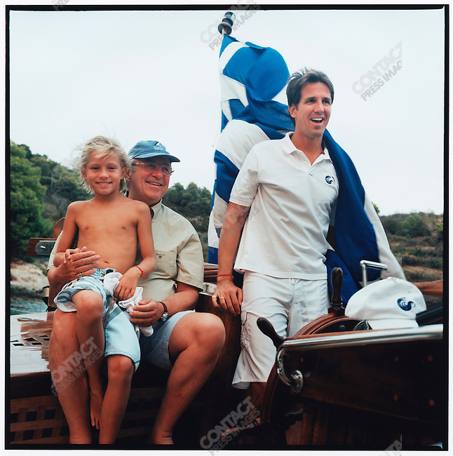 King Constantine II, the former King of the Hellenes,  his son, Prince Pavlos, the Crown Prince of Greece, and the Prince's son, Constantine, on the King's Greek fisherman's sailboat, the Afroesa, during the family's vacation. Porto Heli, Greece, August 2007.