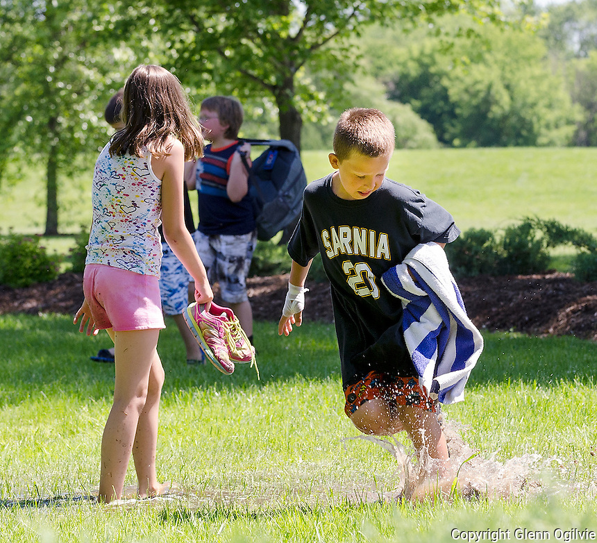Queen Elizabeth II School student  Aiden Inchley makes a splash while walking through Germain Park to Jackson Pool during the Official Opening of Cox Garden and Mary-Ann's Marigold Garden, located at Germain Park.