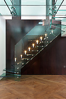 Wall lights illuminate the glass steps of the staircase