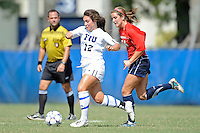 2 October 2011:  FIU's Kelly Ann Hutchinson (12) moves the ball while being pursued by South Alabama's Shawn Meach (54) in the first half as the FIU Golden Panthers defeated the University of South Alabama Jaguars, 2-0, at University Park Stadium in Miami, Florida.