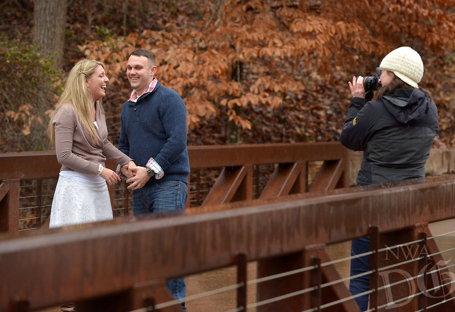 STAFF PHOTO BEN GOFF  @NWABenGoff -- 12/27/14 Lindsay Ost of Lazer Lee Photography in Rogers takes pictures of Jeremy Gunter and fiancé Amanda Kirk, both of Sarasota, Fla., after Gunter proposed on the trails at Crystal Bridges Museum of American Art in Bentonville on Saturday Dec. 27, 2014. Gunter recruited family and friends to help arrange the surprise while the couple was in town for the holidays.