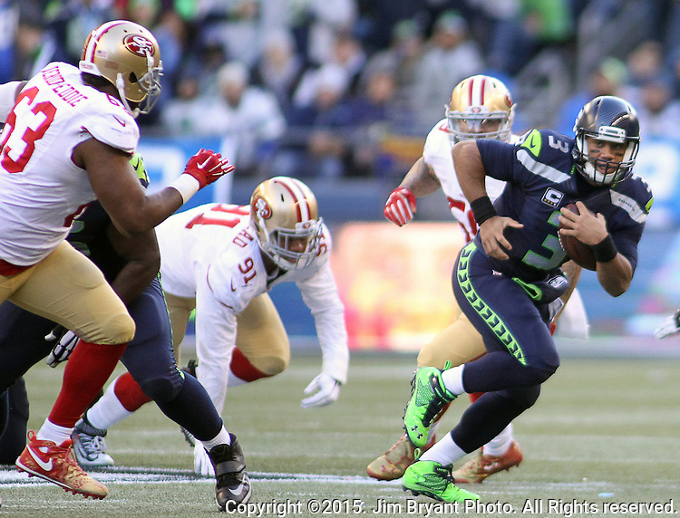 Seattle Seahawks quarterback Russell Wilson (3)  scrambles away from San Francisco 49ers defensive tackle  Arik Armstead (91) and defensive tackle Tony Jerod-Eddie (63) at CenturyLink Field in Seattle, Washington on November 22, 2015.  The Seahawks beat the 49ers 29-13.   ©2015. Jim Bryant Photo. All RIghts Reserved.