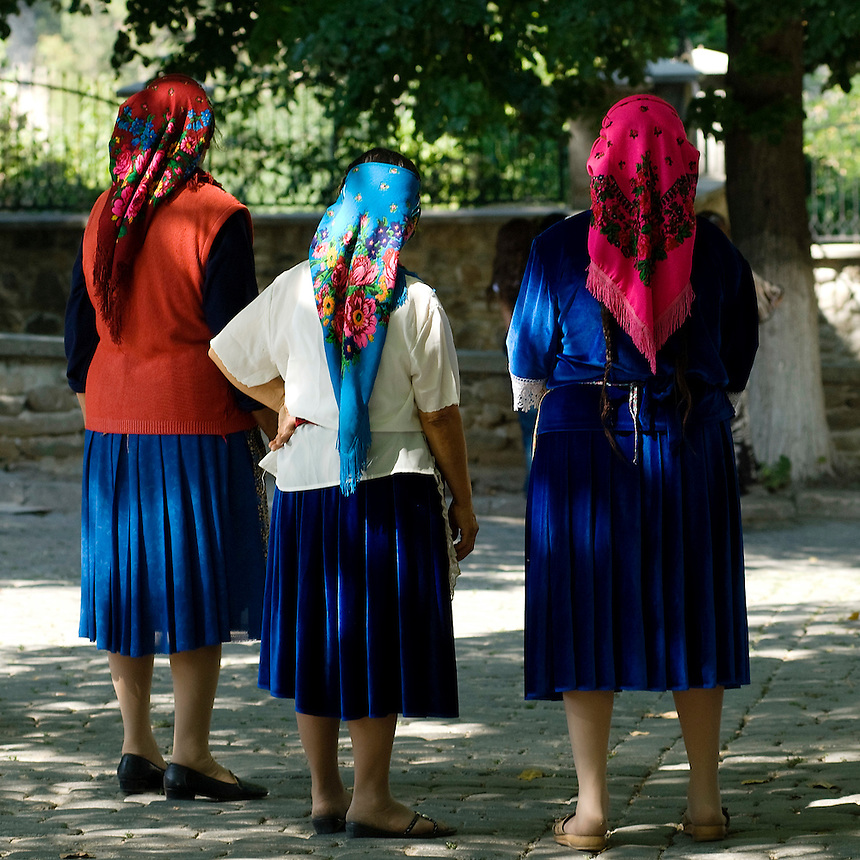 "Old women dressed in traditional Tinsmith costume, wearing colorful headscarf, traditional signs of a married woman at the annual ""bride market"" at Bachkovo monastery, near Plovdiv, Bulgaria. The Tinsmiths are spread all over the country. Holydays, like the  day of Assumption of the Virgin Mary are one of the reasons for them to gather together. Though the annual reunion is known as the Tinsmith's ""bride market"", many people come here just to meet each other. Some extended families sit and chat while young people walk around talking to their peers."