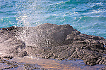 Waves splash violently against rocks in Hawaii.Water shoots out of Spouting Horn.