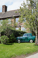 Exterior of a large house from the 1600s. A green Austin A30 is parked on the lawn in front of a hedge.