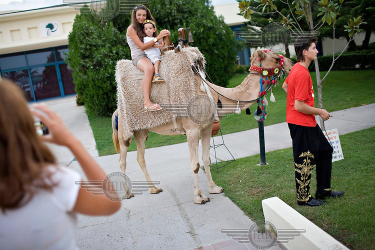Tousits enjoy a camel ride through the grounds of the Majesty Mirage Park Hotel.
