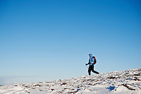 Female hiker hiking on snowy mountain terrain, Brecon Beacons national park, Wales