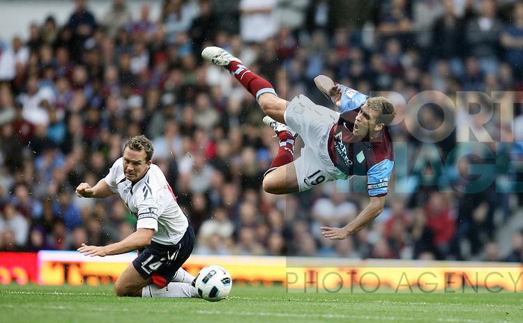 Stiliyan Petrov of Aston Villa is sent flying following a challenge from Bilton's Kevin Davies (l).