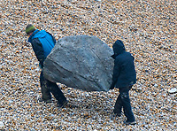 BNPS.co.uk (01202 558833)<br /> Pic: Graham Hunt/BNPS<br /> <br /> Hard labour - moving a rock during filming on the Beach at Eype near Bridport in Dorset yesterday for the new film Ammonite about the life of fossil hunter Mary Anning.