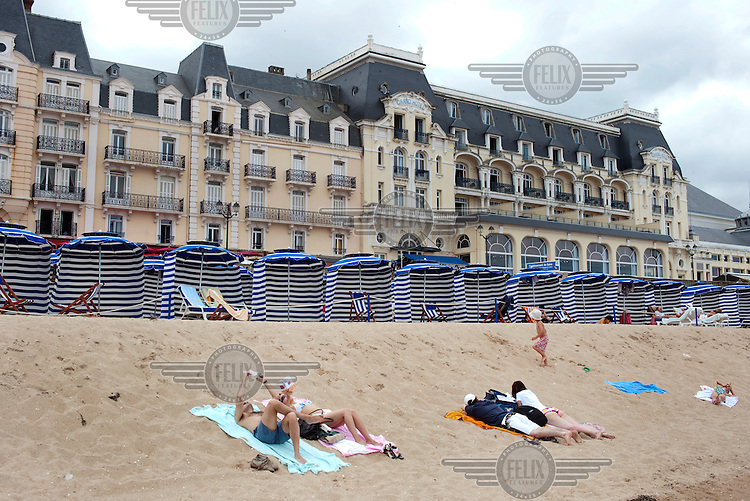 People relax on a beach in front of beach huts and the Grand Hotel in Cabourg.