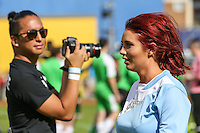 London, UK on Sunday 31st August, 2014. A photographer watches with interest as Amy Childs walks past during the Soccer Six charity celebrity football tournament at Mile End Stadium, London.