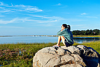 Thoughtful woman enjoying the coastal view from a boulder.